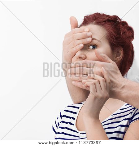 Man's Hands Covering Caucasian Redhair Woman's Mouth And One Eye