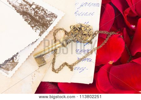 Key with rose petals and old mail
