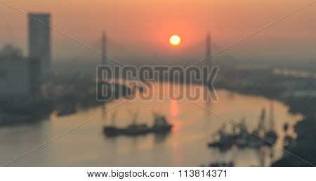 Abstract Blurred Photo Of Riverside Cityscape With Sunrise Over Bridge