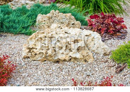 Flowerbed With Stones And Bushes As A Decorative Elements.