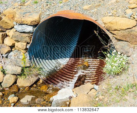 Rusted Corrugated Metal Pipe In Rocky Ground