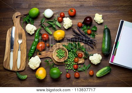 Healthy food. Herbs and vegetables on wooden table with recipe book. Top view.