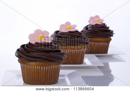 chocolate frosted white cup  cakes with pink royal icing flower on top on white plates