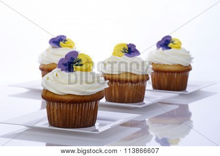 Four vanilla cup cakes white frosting on white plates reflective surface