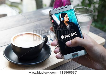 CHIANG MAI THAILAND - JAN 4 2016: A man hand holding screen shot of Apple music app showing on samsung galaxy s6 edge. Apple Music is a beta version on android.