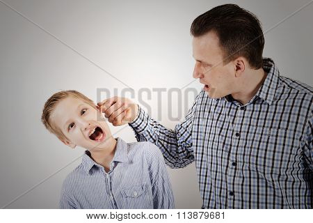 Strict Father Punishes His Son.