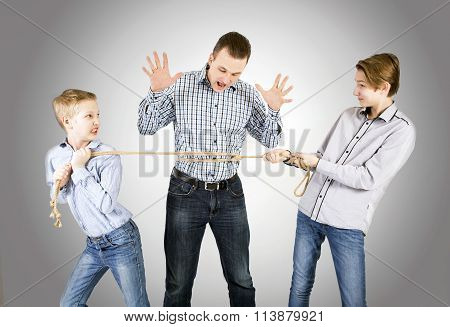 Caucasian siblings boys tied father rope and pull him isolated on white background. Concept of emotions.