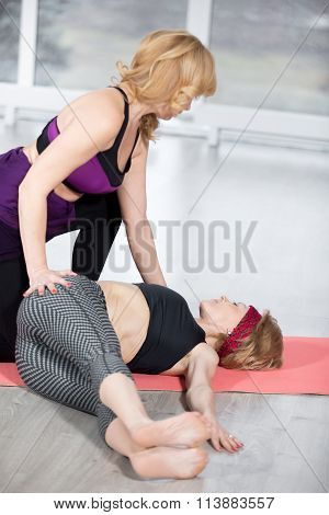 Trainer Helping Student To Do Revolved Abdomen Pose