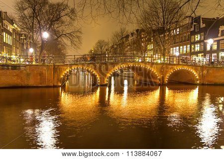 Amsterdam canal and bridge at night