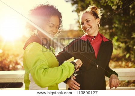 Two Sportswomen In Park, Smiling And Looking At Watch.