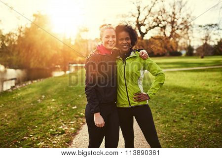 Two Sportswomen In Park Hugging And Looking At Camera