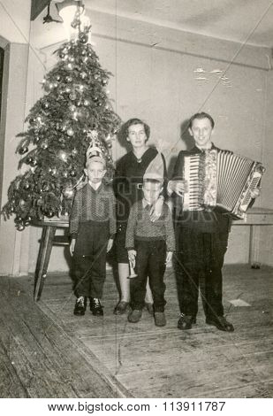 KATOWICE, POLAND, CIRCA 1939: Vintage photo of family with accordion posing in front of Christmas tree