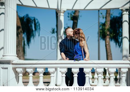 Lovely young couple cuddling in the summer alcove.