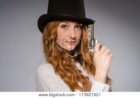 Pretty girl wearing retro hat and holding weapon isolated on gra