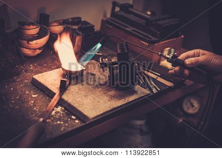 Goldsmith melting gold to liquid state in crucible with gasoline burner. t-shirt