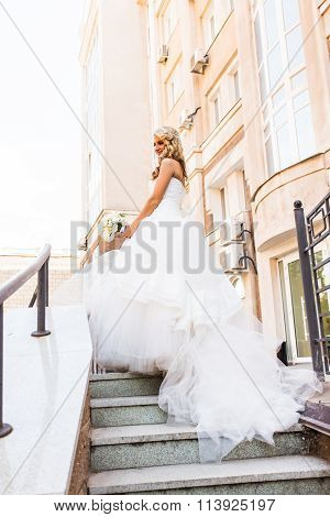 Beautiful bride in magnificent dress stands alone on stairs. poster