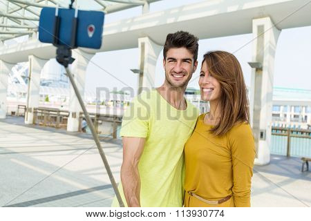 Young couple use selfie stick for taking photo together