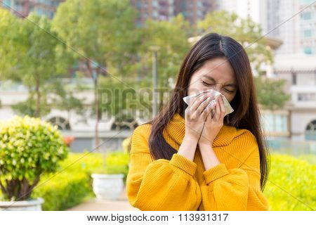 Woman sneezing at outdoor