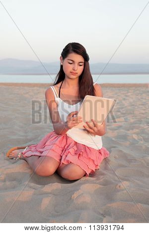 Young european teenage girl with long dark hair browsing on a computer tablet device on a beach in summer.