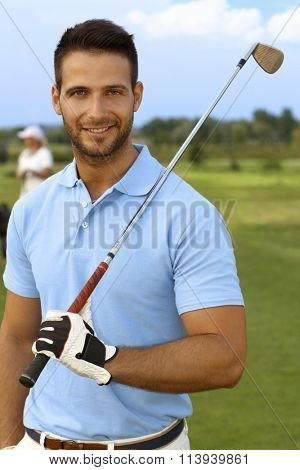 Closeup portrait of goodlooking young male golfer with golf club, smiling, looking at camera.
