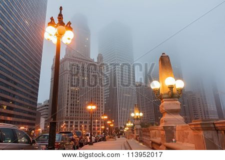 Chicago Street As Mist Descends And Lights Come On Upper Wacker Drive With Ornate Lights Tall Buildi