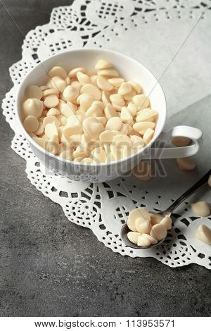 White chocolate morsels in cup on gray background