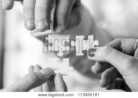 Black And White Image Of Three People Holding Puzzle Pieces To Match Them