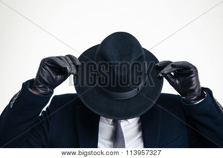 Closeup of black hat weared on business person in black suit and holded by hands in modern black gloves over white background