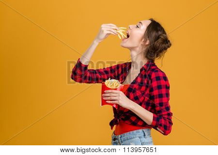 Profile of beautiful happy woman in plaid shirt tasting french fries over yellow background