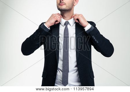 Confident attractive young businessman adjusting his collar over white background