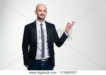Smiling handsome businessman standing and pointing away over white background