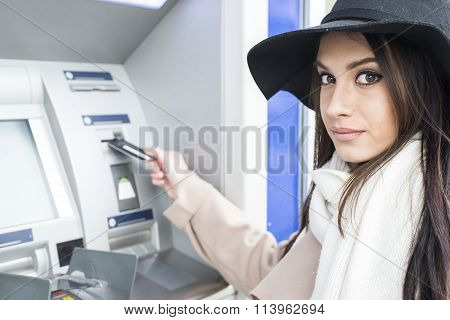 Young pretty woman using the ATM outside