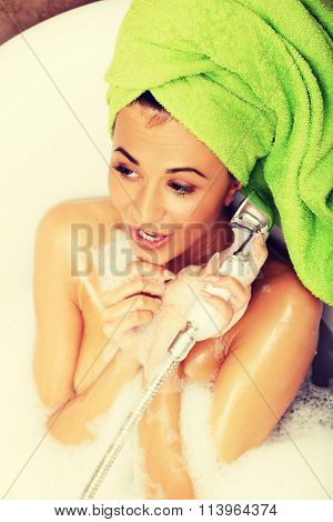 Woman having fun with showerhead