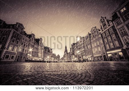Cobblestone historic old town in rain. The market square at night. Wroclaw, Poland in vintage, nostalgic mood. Perfect empty space to put your object on the ground.