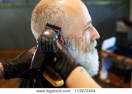 sideview portrait of senior bearded man in professional barbershop. barber shaving beard with electric razor