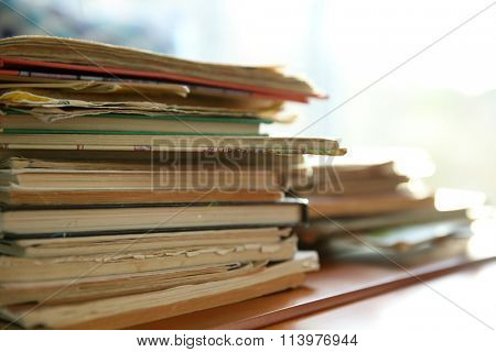 Pile of old books on brown table in the room, close up