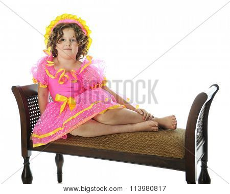 An elementary Shirley Temple impersonator happily sitting mermaid-style on a padded bench. On a white background.