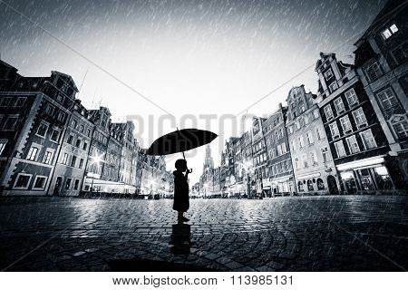 Child with umbrella standing alone on cobblestone old town in rain. Concept of being lost, lonely in a big world or exploring