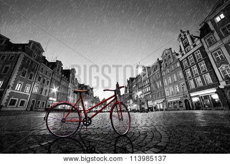 Vintage red bike on cobblestone historic old town in rain. Color in black and white. The market square at night. Wroclaw, Poland.