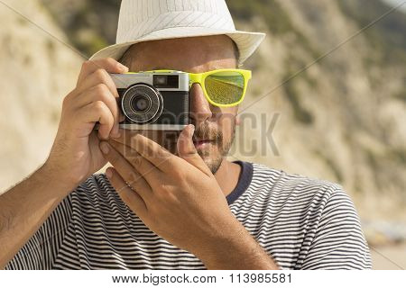 Tourist taking a photo on the beach by using retro camera