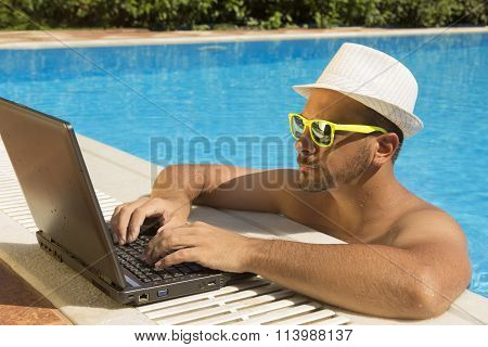 Man working on laptop at the swimming pool edge