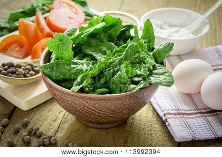 Spinach Leaves In A Bowl On A Background Of Food On A Wooden Table
