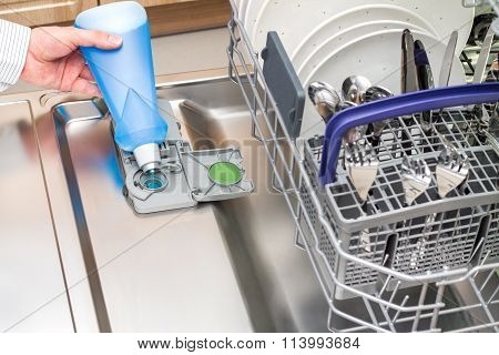 Man pours a Rinse Aid into the dishwasher