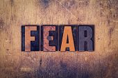 """The word """"Fear"""" written in dirty vintage letterpress type on a aged wooden background. poster"""