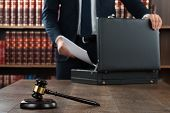 Midsection of lawyer putting documents in briefcase with gavel at desk in courtroom poster