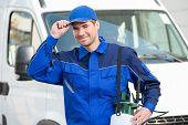 Portrait of confident pest control worker wearing cap against truck poster