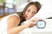 Happy woman waking up and turning off the alarm clock having a good day poster