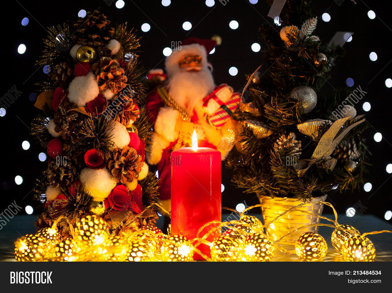 Two Mini Christmas Trees And A Santa Claus Figurine On Black Background With Bokeh Lights On