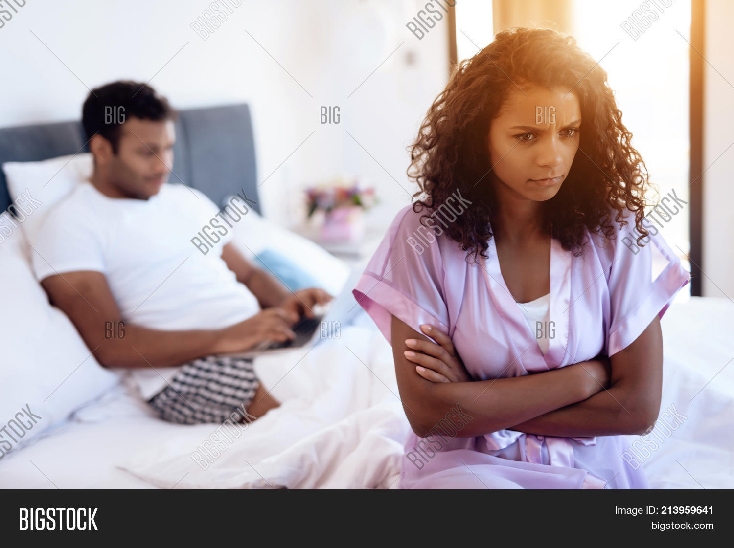 fe81f4678af8 Black man and woman in the bedroom. A man is lying on the bed with