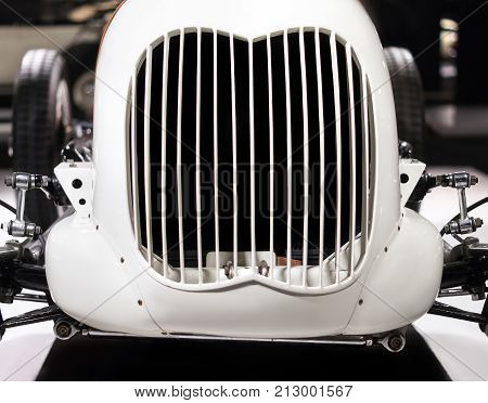 Grid grille in the hood of vintage racing car close up. Front side